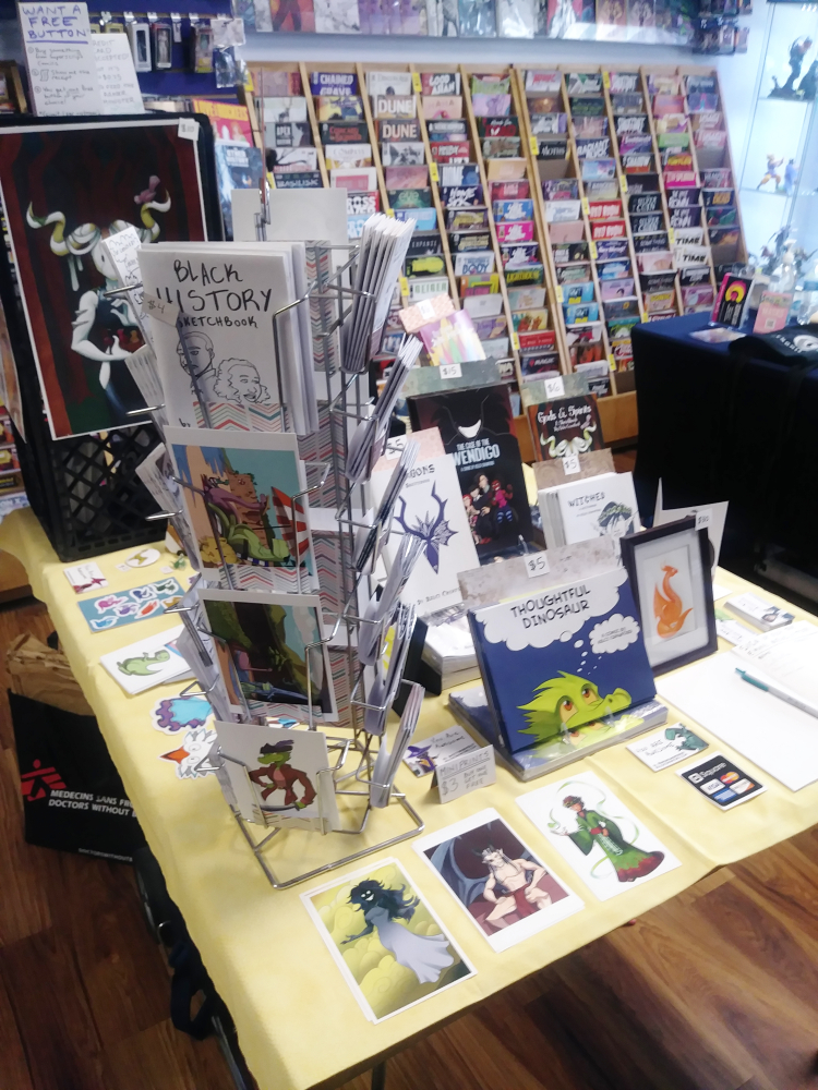 pictured is an artist alley table set up at a mini pop up event hosted by Genghis Con. This event happened at Superscript Comics and Games in Lakewood, OH.